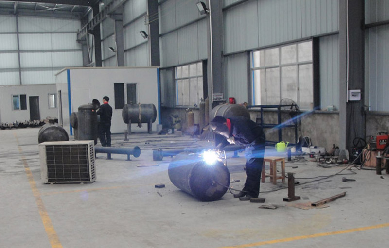 Skilled workers are working on cast iron pressure tanks